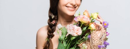 Photo for Cropped view of happy beautiful woman with braid in mesh with spring wildflowers isolated on grey - Royalty Free Image