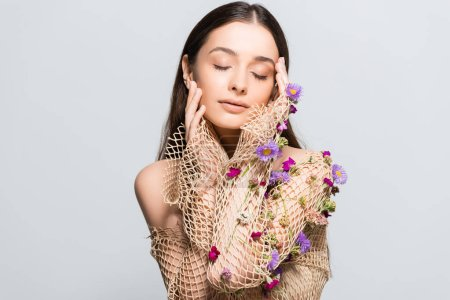 Photo for Beautiful woman with closed eyes in mesh beige clothing with purple flowers touching face isolated on grey with copy space - Royalty Free Image
