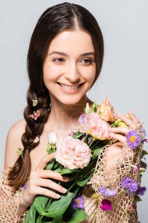 Photo pour Heureuse belle femme avec tresse en maille avec printemps fleurs sauvages isolées sur gris - image libre de droit