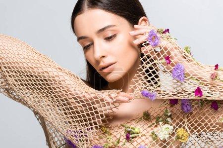 Photo pour Belle jeune femme en mesh beige vêtements avec des fleurs violettes posant isolé sur gris - image libre de droit