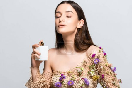 Photo for Beautiful woman in mesh clothing with purple flowers spraying perfume with floral scent on skin isolated on grey - Royalty Free Image