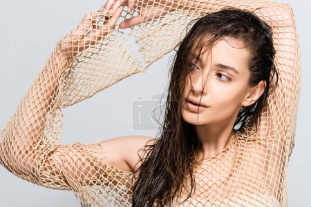 Photo for Beautiful woman with wet hair in mesh beige clothing posing isolated on grey - Royalty Free Image