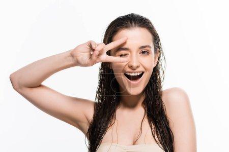 Photo pour Belle jeune femme humide clin d'œil et montrant signe de paix isolé sur le blanc - image libre de droit