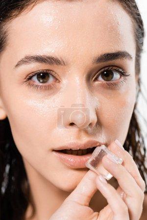 Foto de Portrait of brunette wet young woman holding ice cube near lips isolated on white - Imagen libre de derechos