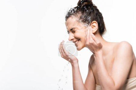 Photo pour Heureuse jeune femme brune avec beauté naturelle se laver avec de l'eau propre éclaboussure isolé sur blanc - image libre de droit