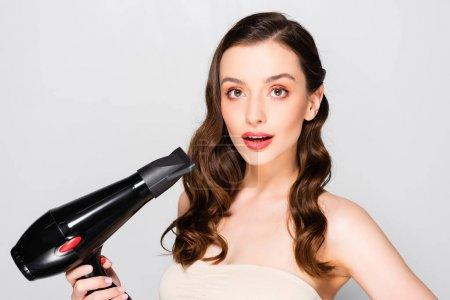 Foto de Beautiful brunette young woman with curls and makeup holding hairdryer isolated on grey - Imagen libre de derechos