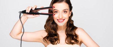 Foto de Happy beautiful brunette woman with curls and makeup holding straightening flat iron isolated on grey, panoramic shot - Imagen libre de derechos