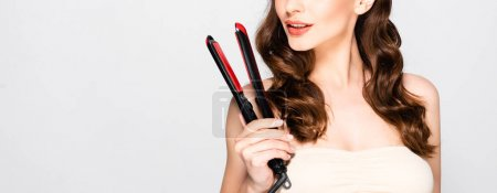 Photo for Cropped view of beautiful brunette woman with curls holding straightening flat iron isolated on grey, panoramic shot - Royalty Free Image
