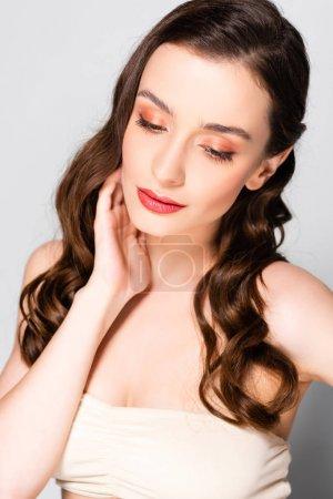 Foto de Beautiful brunette woman with curls and makeup looking down isolated on grey - Imagen libre de derechos