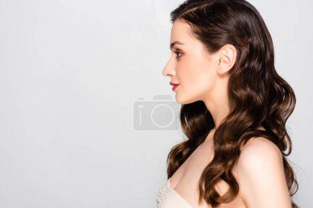 Photo pour Vue latérale de belle femme brune avec boucles et maquillage isolé sur gris - image libre de droit