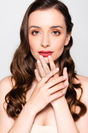 Photo pour Belle femme brune avec des boucles et le maquillage touchant des lèvres d'isolement sur le gris - image libre de droit