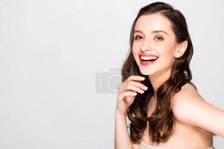 Foto de Happy beautiful brunette woman with curls and makeup laughing isolated on grey - Imagen libre de derechos
