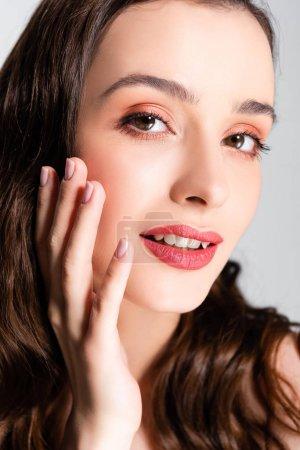 Photo pour Belle femme brune avec boucles et maquillage touchant visage isolé sur gris - image libre de droit
