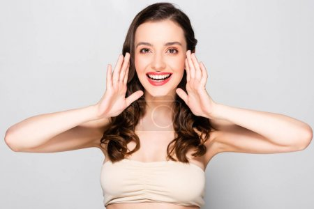 Photo for Happy beautiful brunette woman with curls and makeup posing with hands near face isolated on grey - Royalty Free Image