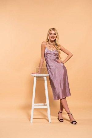 Photo pour Belle femme blonde de sourire dans la robe de satin violet posant près de la chaise élevée blanche sur le fond beige - image libre de droit