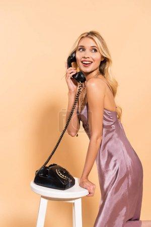 smiling beautiful blonde woman in violet satin dress talking on black retro phone on beige background