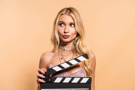 Photo for Blonde woman in violet satin dress with movie clapper board looking away on beige background - Royalty Free Image