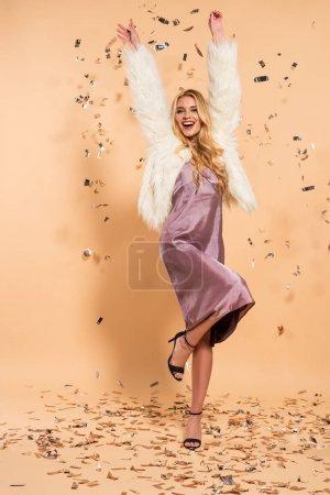 Photo pour Femme blonde heureuse dans la robe violette de satin et le manteau de fausse fourrure dansant sous les confettis tombants argentés sur le fond beige - image libre de droit