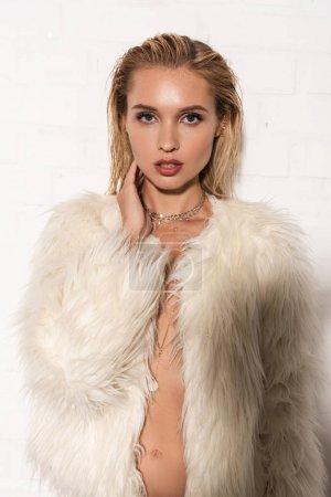 Photo pour Jeune femme nue sexy dans le manteau blanc de fausse fourrure sur le fond blanc - image libre de droit