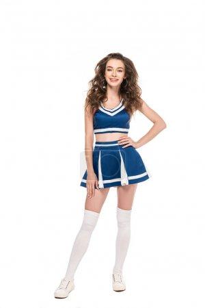 Photo pour Sexy heureux cheerleader fille en uniforme bleu avec la main sur la hanche isolé sur blanc - image libre de droit