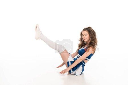 Photo pour Sexy cheerleader fille en uniforme bleu dansant tout en étant assis sur le sol isolé sur blanc - image libre de droit