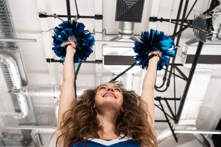 Photo for Bottom view of happy cheerleader girl in blue uniform dancing with pompoms - Royalty Free Image