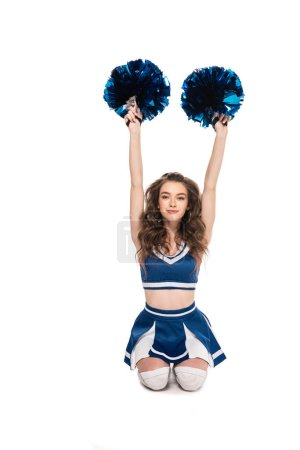 Photo for Cheerleader girl in blue uniform sitting with pompoms and hands in air on floor isolated on white - Royalty Free Image