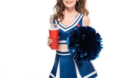 Photo pour Vue recadrée de joyeuse pom-pom girl en uniforme bleu tenant pompon et soda dans une tasse en papier isolé sur blanc - image libre de droit