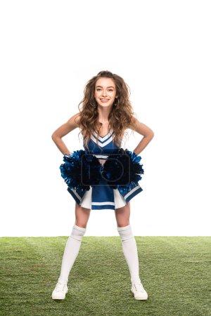 Photo pour Excité cheerleader fille en uniforme bleu avec pompons sur champ vert isolé sur blanc - image libre de droit