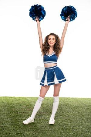Photo pour Fille heureuse sexy de pom-pom girl dans l'uniforme bleu avec des pompons dans des mains sur le domaine vert d'isolement sur le blanc - image libre de droit