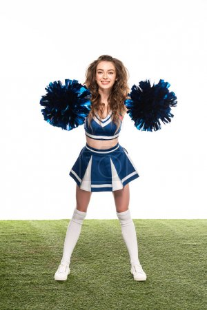 Photo for Happy cheerleader girl in blue uniform dancing with pompoms on green field isolated on white - Royalty Free Image
