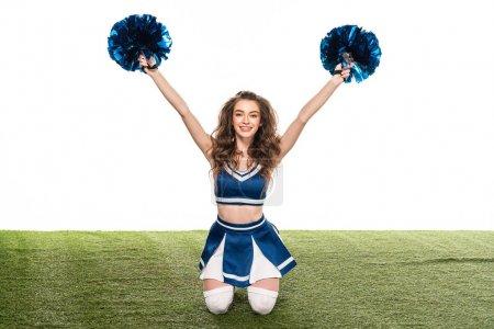 Photo pour Fille heureuse sexy de pom-pom girl dans l'uniforme bleu se reposant avec des pompons dans des mains sur le domaine vert d'isolement sur le blanc - image libre de droit