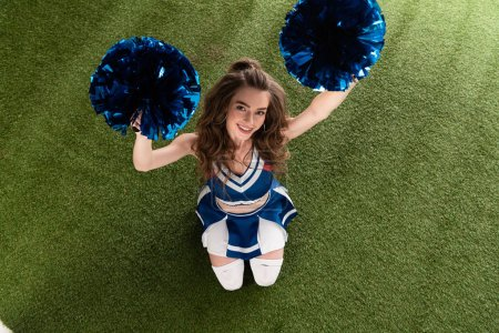 Photo for Top view of smiling cheerleader girl in blue uniform sitting with pompoms on green field - Royalty Free Image