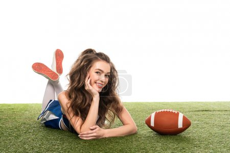 Photo for Happy cheerleader girl in blue uniform lying near rugby ball on green field isolated on white - Royalty Free Image