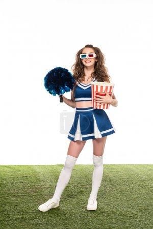 Photo pour Fille heureuse de pom-pom girl dans l'uniforme bleu et les glaces 3d restant avec le maïs éclaté et le pompon sur le domaine vert d'isolement sur le blanc - image libre de droit
