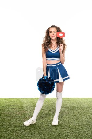 Photo for Happy cheerleader girl in blue uniform with like sign and pompom on green field isolated on white - Royalty Free Image