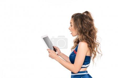 Photo pour Vue latérale de surprise cheerleader fille en uniforme bleu tenant tablette numérique isolé sur blanc - image libre de droit