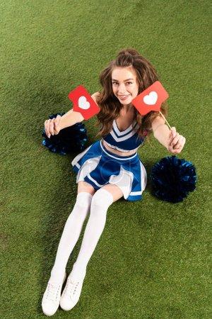 Foto de Vista aérea de la chica alegre animadora en uniforme azul sentado con pompones y corazones de las redes sociales en el campo verde - Imagen libre de derechos