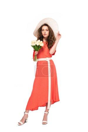 Photo pour Vue pleine longueur de la femme élégante dans le chapeau et la robe retenant les tulipes blanches d'isolement sur le blanc - image libre de droit