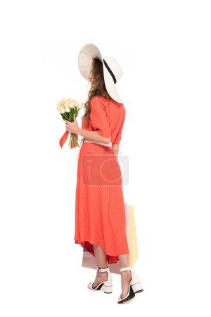Photo pour Vue arrière de la femme élégante dans le chapeau et la robe retenant les tulipes blanches et les sacs à provisions d'isolement sur le blanc - image libre de droit