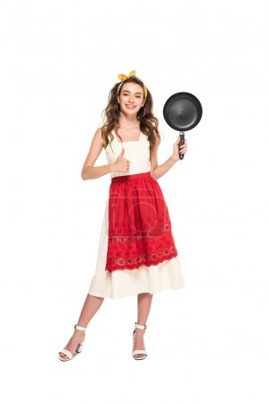 Photo for Full length view of young housewife in dress and apron holding frying pan and showing thumb up isolated on white - Royalty Free Image