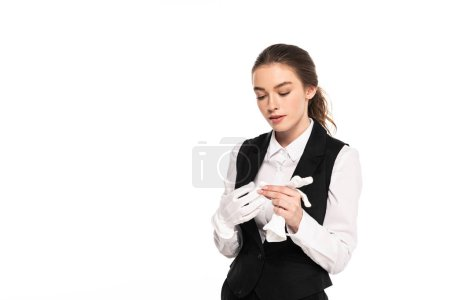 Photo for Young waitress in formal wear looking at white gloves isolated on white - Royalty Free Image