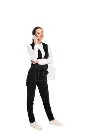 full length view of happy young waitress talking on smartphone isolated on white