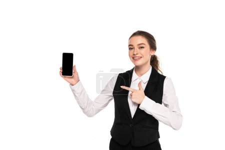 Photo pour Happy young waitress pointing with finger at blank screen on smartphone isolated on white - image libre de droit