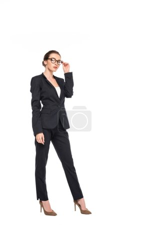 Photo for Full length view of young successful businesswoman in black suit and glasses isolated on white - Royalty Free Image