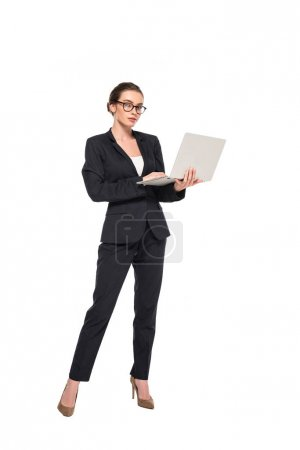 full length view of young successful businesswoman in black suit and glasses with laptop isolated on white
