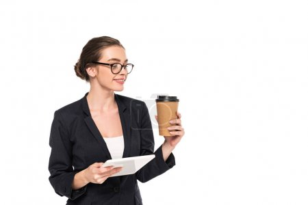 Photo for Young smiling successful businesswoman in black suit and glasses holding coffee to go and digital tablet isolated on white - Royalty Free Image