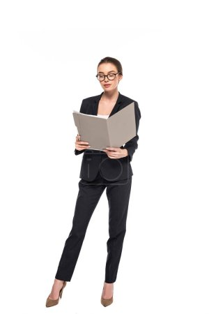 young successful businesswoman in black suit and glasses reading documents in folder isolated on white