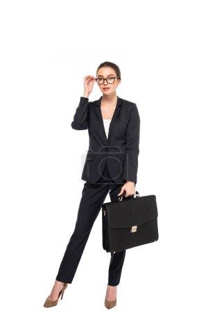 Foto de Vista completa de la joven empresaria de éxito en traje negro y gafas con maletín aislado en blanco - Imagen libre de derechos