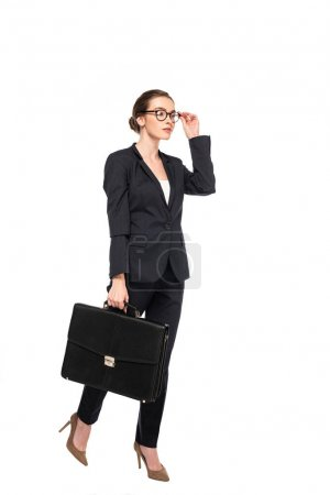 full length view of successful businesswoman in black suit and glasses with briefcase isolated on white
